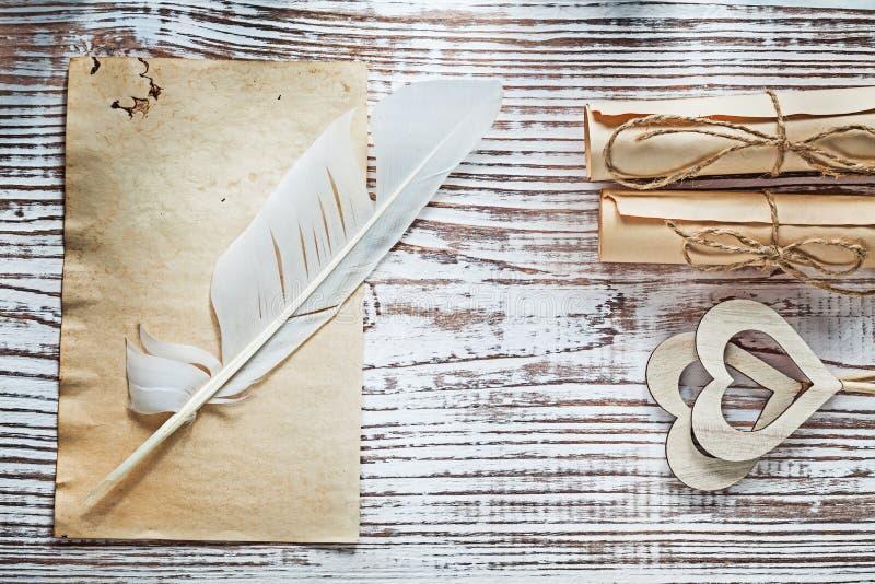 Los rollos medievales del papel de la hoja plume corazones de madera en la madera b del vintage fotos de archivo libres de regalías