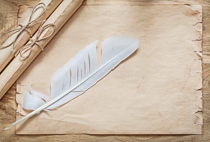Los rollos medievales del papel de pergamino plume en el tablero de madera imagenes de archivo