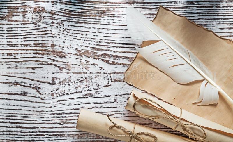 Los rollos medievales del papel de pergamino plume en el tablero de madera del vintage imagen de archivo