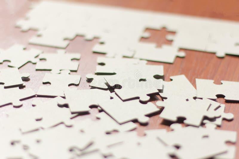 Los rompecabezas dispersaron en los rompecabezas de la tabla, el principio de la asamblea foto de archivo