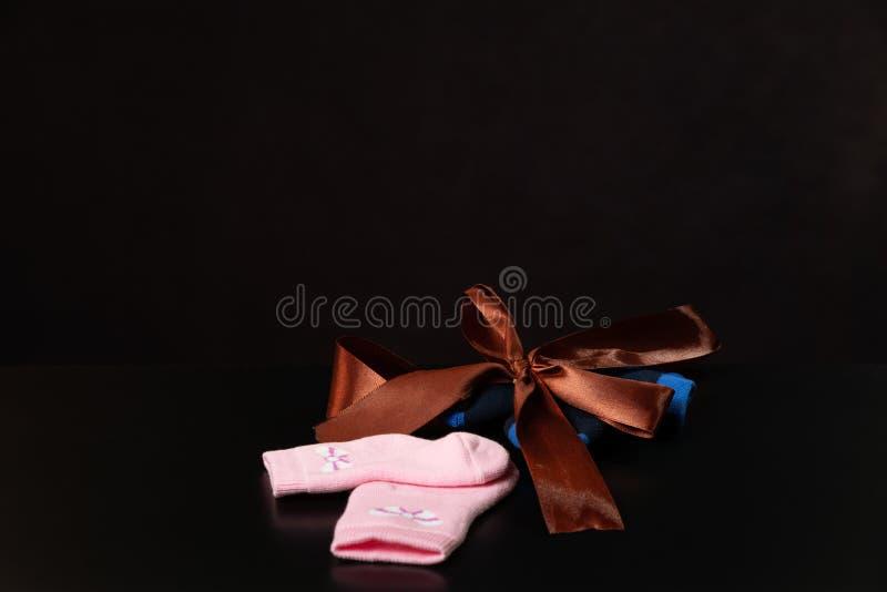 Los rosas bebés y los calcetines azules con un arco están mintiendo en una tabla negra, en un fondo negro foto de archivo