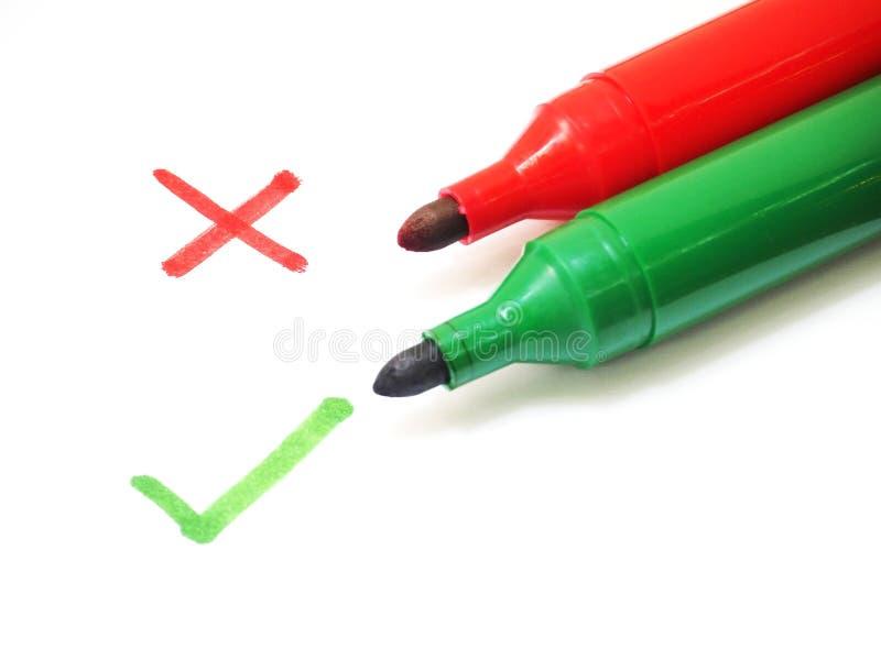 Los rotuladores rojos y verdes con la cruz y la lista de control firman fotos de archivo