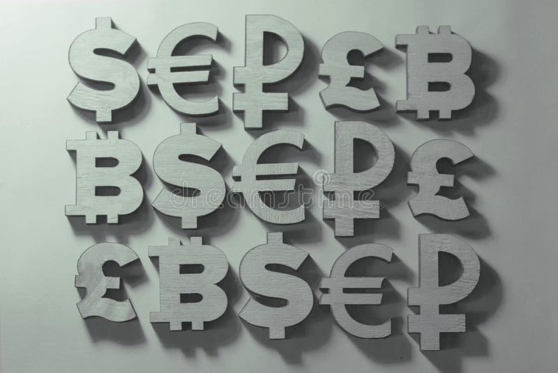 los símbolos del dinero y las monedas del mundo mienten en un fondo gris imagenes de archivo