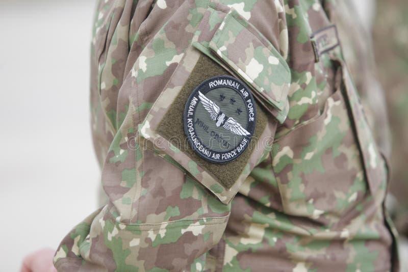 Los símbolos rumanos de la fuerza aérea en un soldado de sexo femenino uniforman foto de archivo