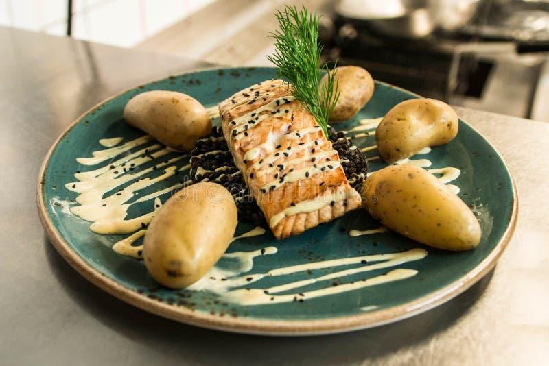 Los salmones asados a la parrilla colocados en una placa con bulgur negro y con las patatas cocinadas arreglaron para la cena fotografía de archivo