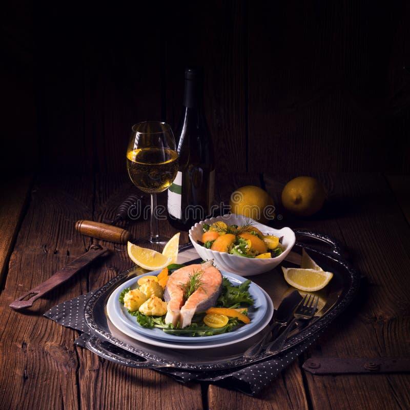 Los salmones con mantequilla frieron el puré y la ensalada de patata foto de archivo libre de regalías