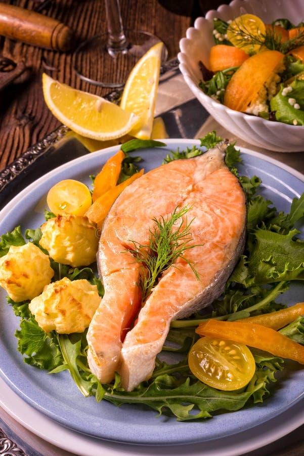 Los salmones con mantequilla frieron el puré y la ensalada de patata imágenes de archivo libres de regalías