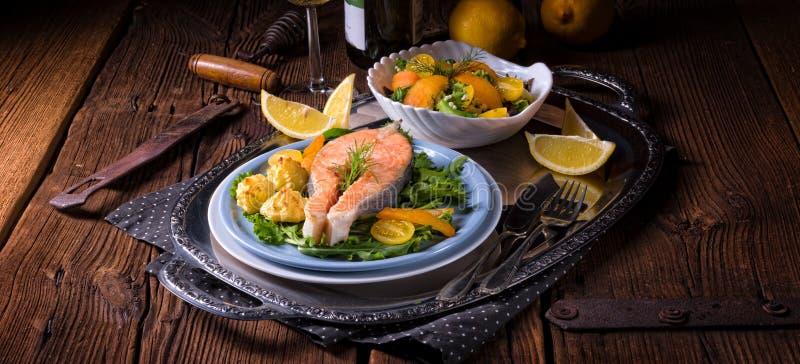 Los salmones con mantequilla frieron el puré y la ensalada de patata imagen de archivo