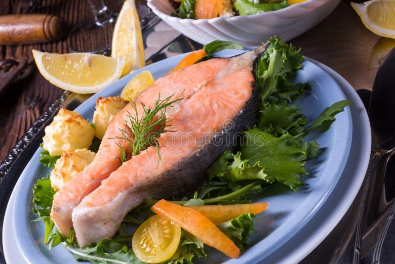 Los salmones con mantequilla frieron el puré y la ensalada de patata fotos de archivo