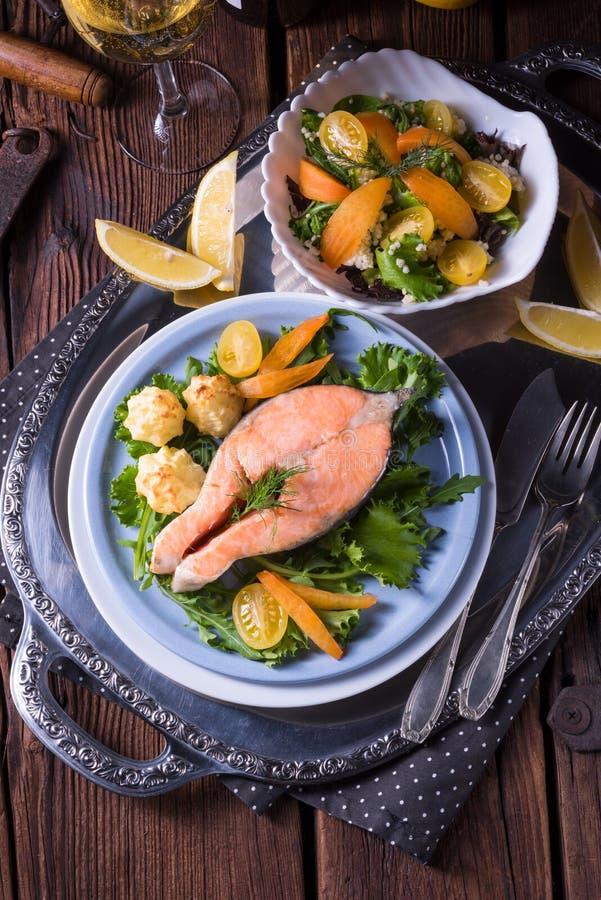 Los salmones con mantequilla frieron el puré y la ensalada de patata fotografía de archivo libre de regalías