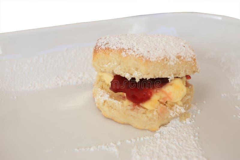 Los scones cocidos frescos con mantequilla y atasco, rematan con la formación de hielo en la placa blanca fotografía de archivo libre de regalías