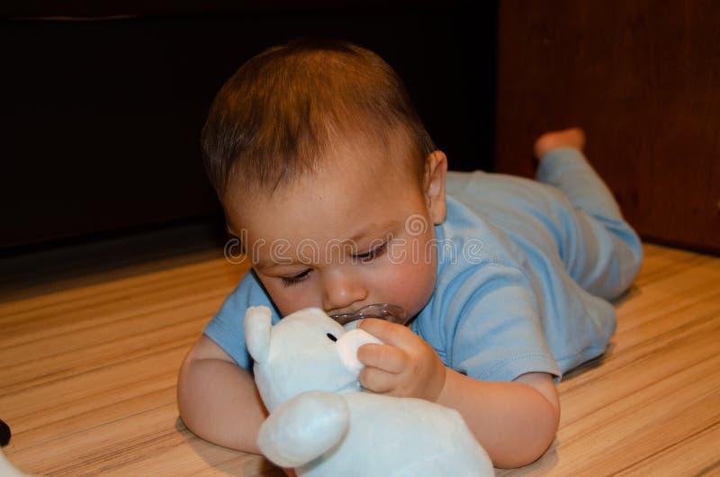 Los seis meses lindos del beb? que juega con el peluche azul refieren el piso, echar los dientes y el concepto temprano del desar imagen de archivo