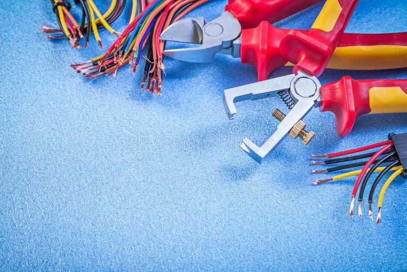 Los separadores del aislamiento fijaron de los alambres eléctricos que cortaban los alicates en azul fotografía de archivo libre de regalías