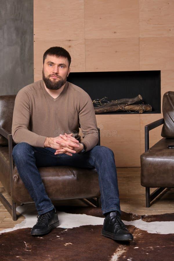 Los sitts serios hermosos jovenes confiados del hombre en la silla de cuero en sala de estar con la mano cruzaron fotos de archivo libres de regalías
