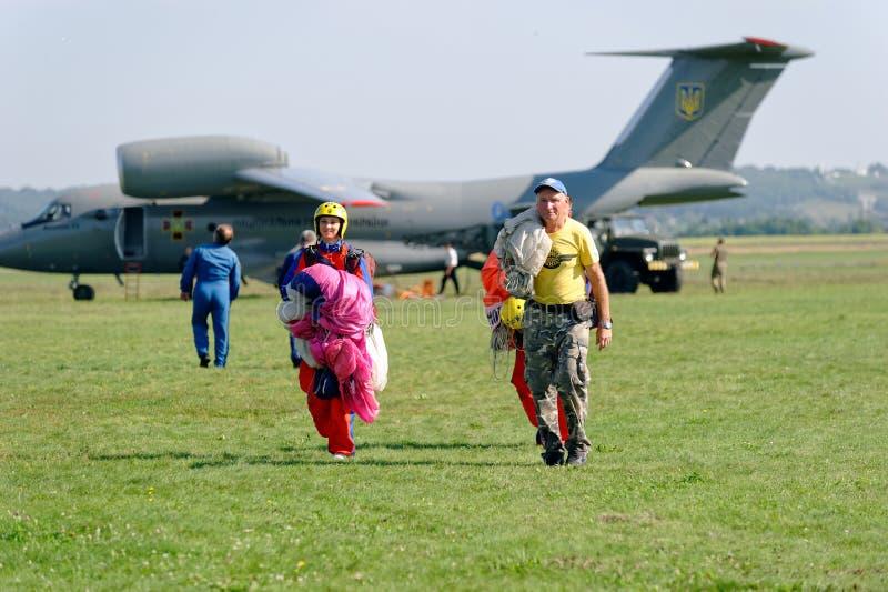 Los Skydivers llevan un paracaídas después de aterrizar fotos de archivo