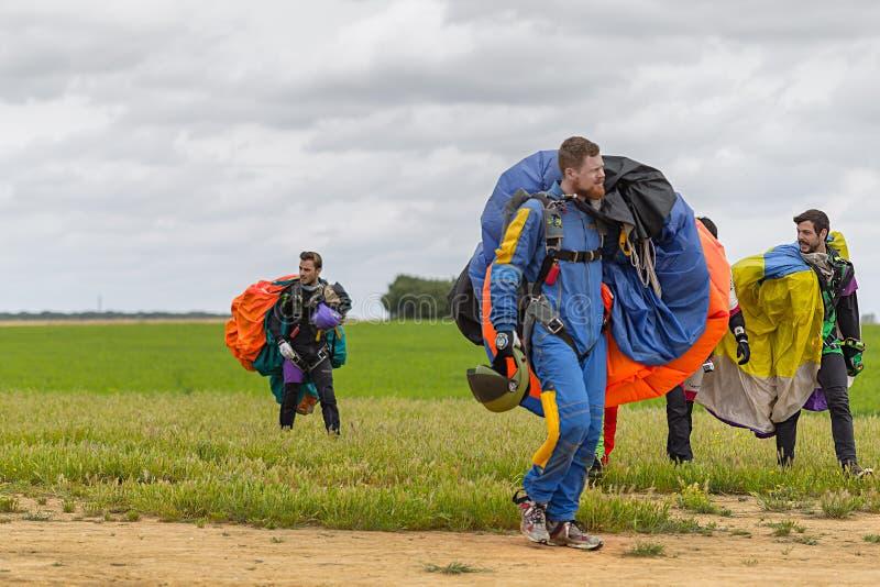 Los Skydivers llevan un paracaídas después de aterrizar imagenes de archivo