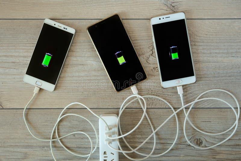 Los smartphones se cargan del cargador y de la mentira de lado a lado foto de archivo libre de regalías