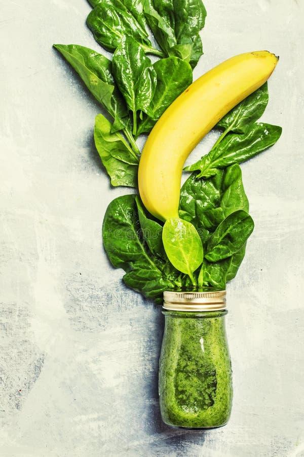 Los smoothies verdes del detox hechos de espinaca se van en una botella de cristal fotos de archivo