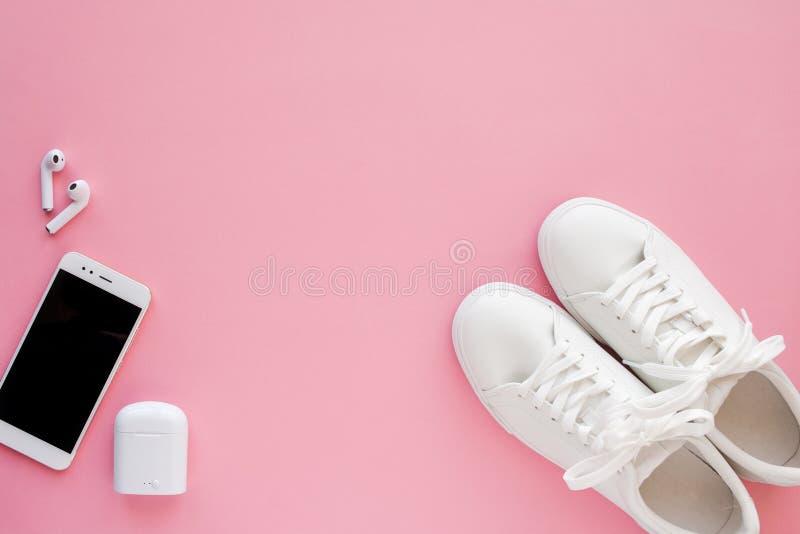 Los sneackers blancos, los auriculares inalámbricos y el smartphone están mintiendo en un fondo rosado imagen de archivo