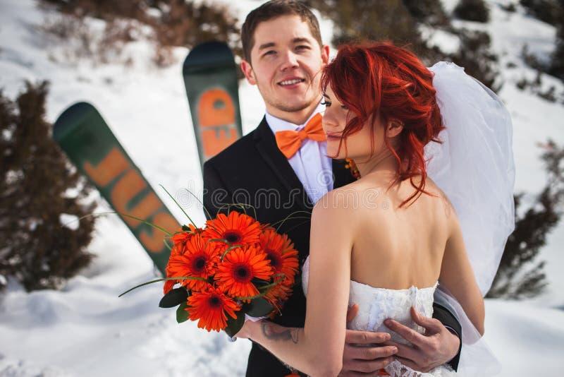 Los snowboarders de la boda se juntan apenas casado en el invierno de la montaña imagenes de archivo
