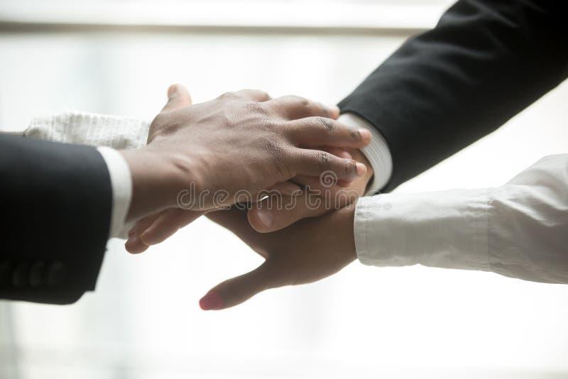 Los socios africanos y caucásicos pusieron las manos juntas, cerca encima de la visión foto de archivo libre de regalías