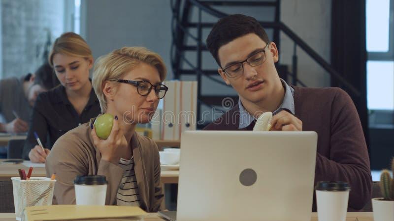 Los socios comerciales jovenes están descansando en oficina, comiendo las frutas y hablar fotos de archivo libres de regalías
