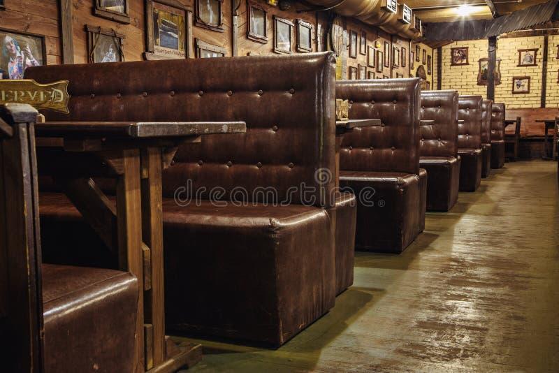los sofás de cuero en las tablas están en un pub de la cerveza o en un club nocturno imagenes de archivo