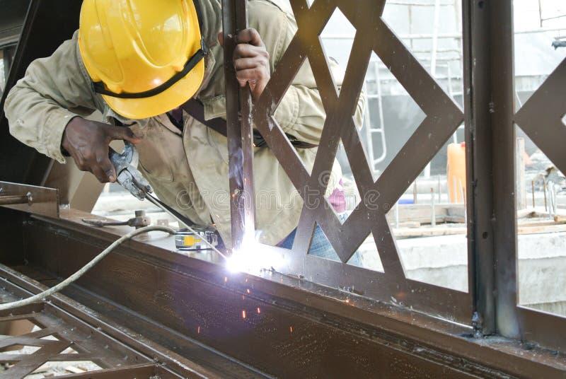 Los soldadores soldaron con autógena el acero suave decorativo en el emplazamiento de la obra foto de archivo libre de regalías
