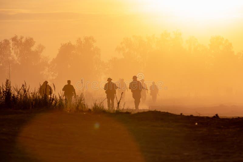 Los soldados de la acción de la silueta que caminan las armas del control el fondo son humo y puesta del sol Guerra, militares y  imagen de archivo libre de regalías