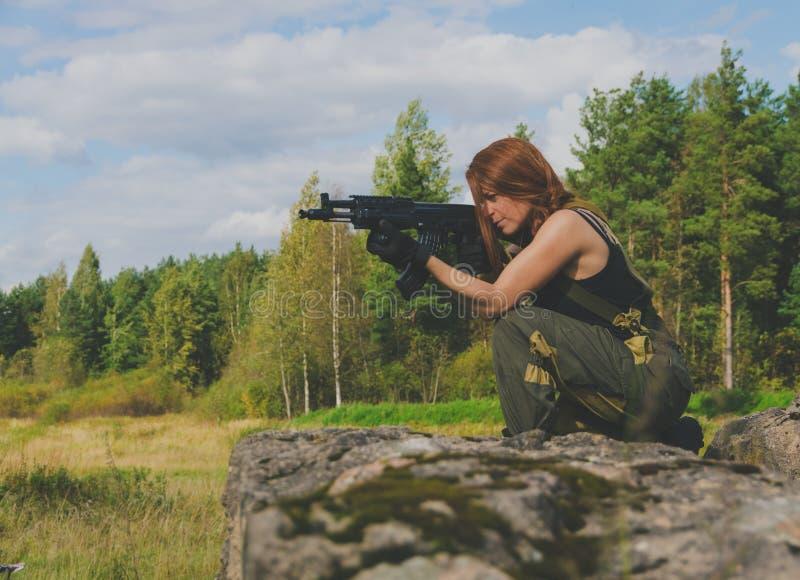 Los soldados de la muchacha toman objetivo del arma que está en una colina foto de archivo libre de regalías