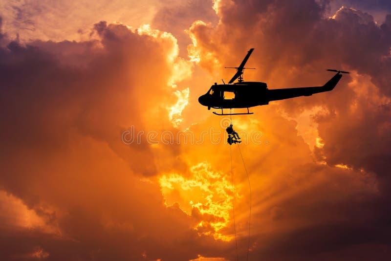 Los soldados de la silueta en la acción rappelling suben abajo del helicóptero con el entrenamiento de asalto del terrorismo del  imágenes de archivo libres de regalías