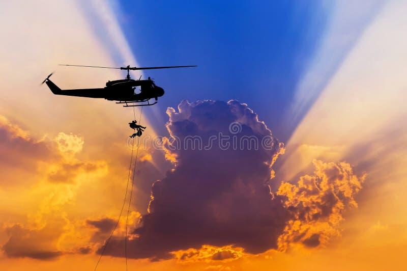 Los soldados de la silueta en la acción rappelling suben abajo del helicóptero con el entrenamiento de asalto del terrorismo del  fotos de archivo