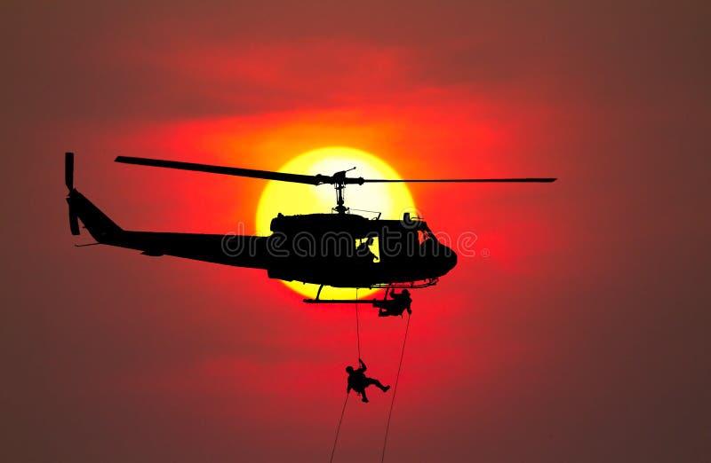 Los soldados de la silueta rappel abajo para atacar del helicóptero con el guerrero para guardarse de peligro en la falta de defi fotografía de archivo libre de regalías