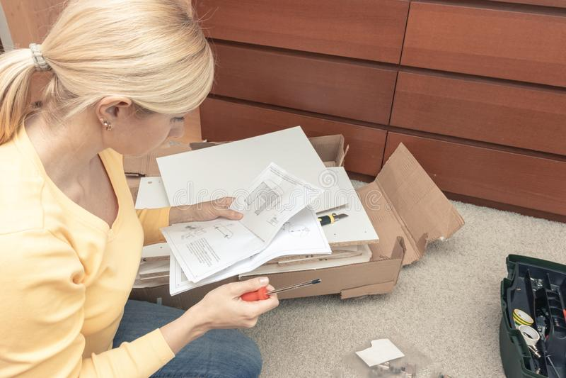 Los solos pedazos de junta de la mujer joven de nuevos muebles y de leer la instrucción, las cajas abiertas con los detalles de l foto de archivo libre de regalías