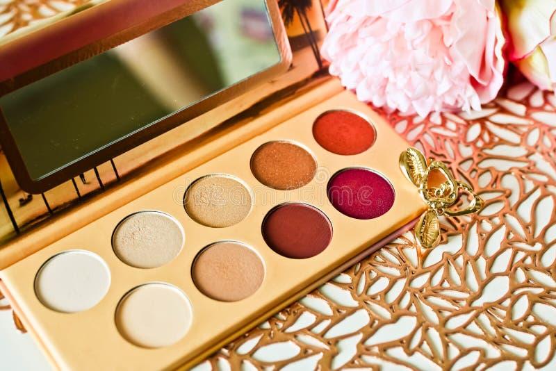 Los sombreadores de ojos multicolores fijados en el oro modelaron el fondo con las flores rosadas y los pendientes de oro Elegant fotografía de archivo libre de regalías