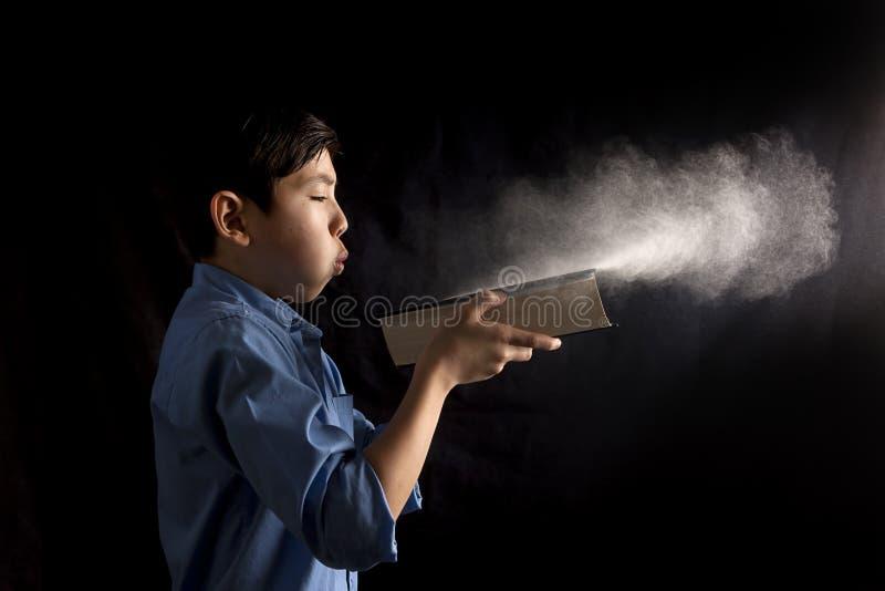 Los soplos del muchacho sacan el polvo apagado del libro fotos de archivo