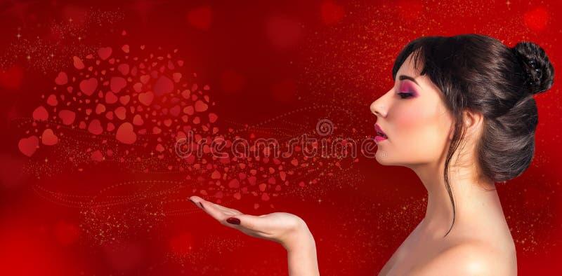 Los soplos hermosos de una mujer en su mano y corazones rojos vuelan en un holi imagen de archivo