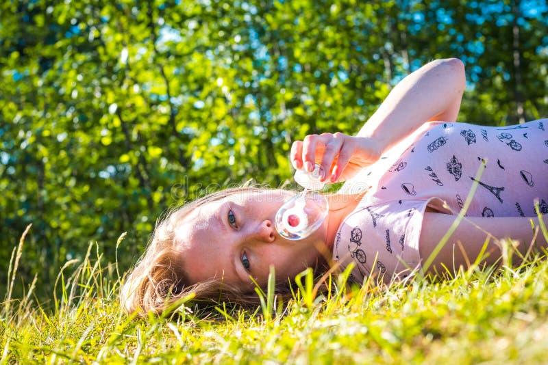 Los soplos hermosos y de la chica joven jabonan burbujas imagenes de archivo