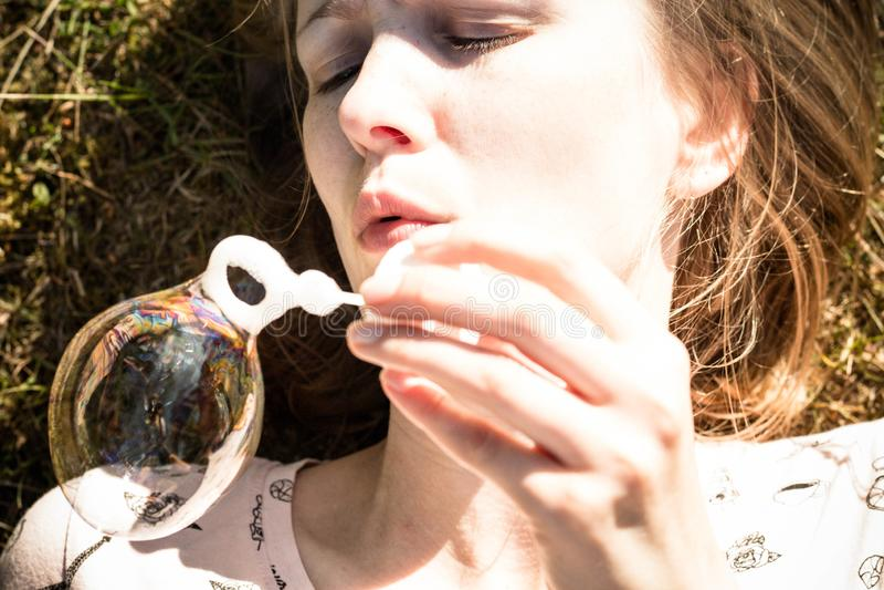 Los soplos hermosos y de la chica joven jabonan burbujas fotografía de archivo