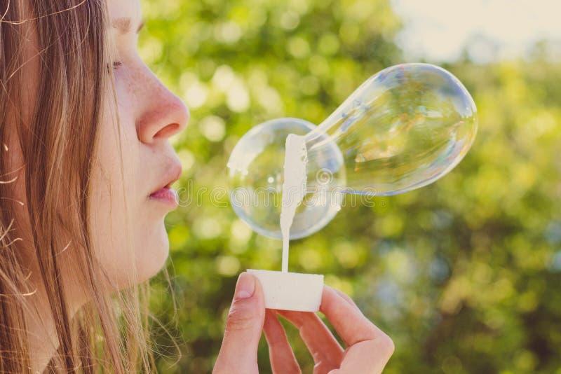 Los soplos hermosos y de la chica joven jabonan burbujas fotos de archivo libres de regalías
