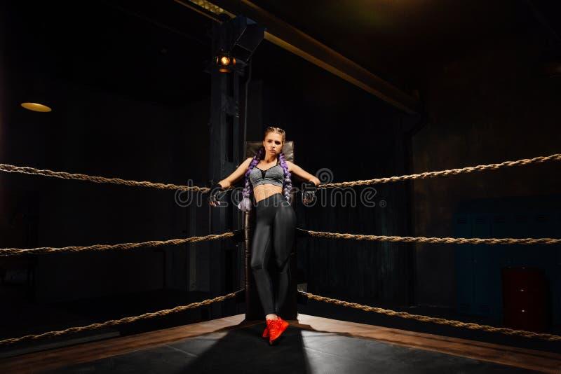 Los soportes atractivos de la muchacha del boxeo se inclinaron en cuerdas del anillo de la competencia fotos de archivo libres de regalías