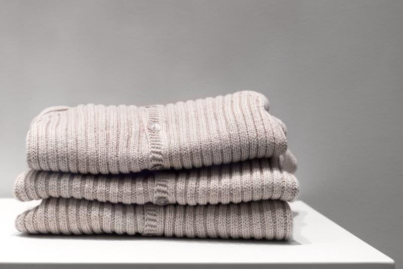 Los suéteres beige hicieron de telas naturales se doblan en la tabla imagen de archivo libre de regalías