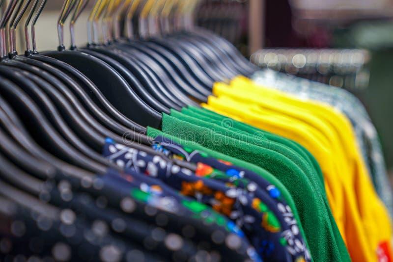 Los suéteres de la variedad caída de la marca encendido a la suspensión en la tienda del paño de la moda en grandes almacenes foto de archivo libre de regalías