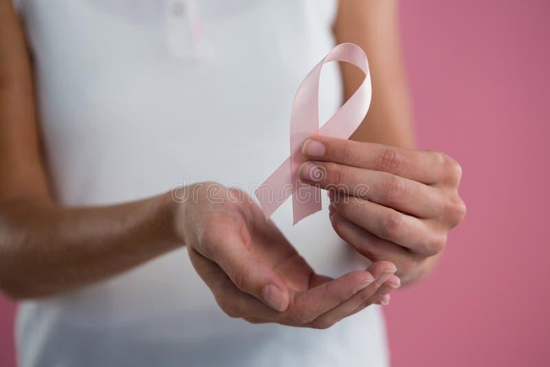 Los supervivientes mandan un SMS y dan a sostener la tarjeta con las mujeres rosadas de la conciencia del cáncer de pecho fotos de archivo libres de regalías