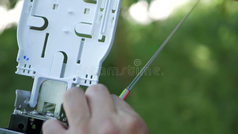 Los técnicos están instalando la fibra óptica con las bridas de plástico fotografía de archivo libre de regalías