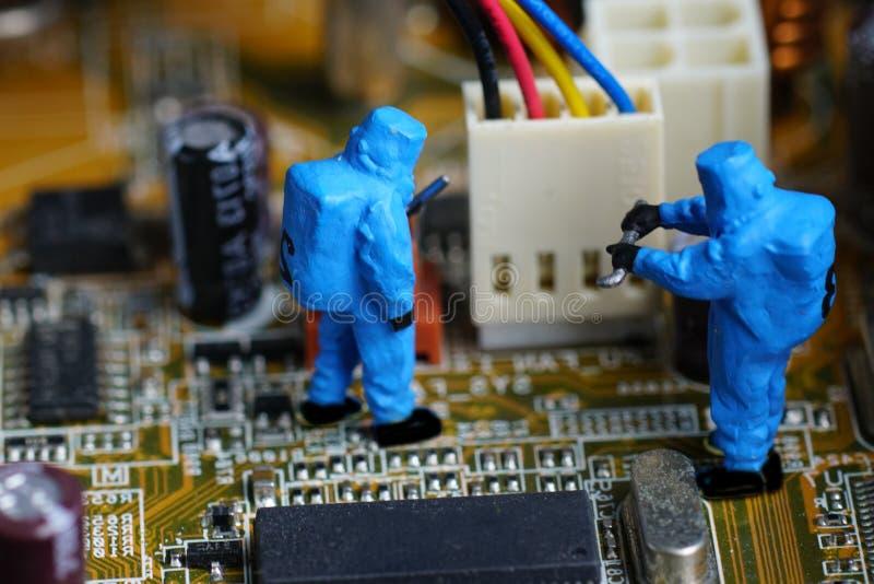 Los técnicos reparan en mainboard del ordenador imagenes de archivo