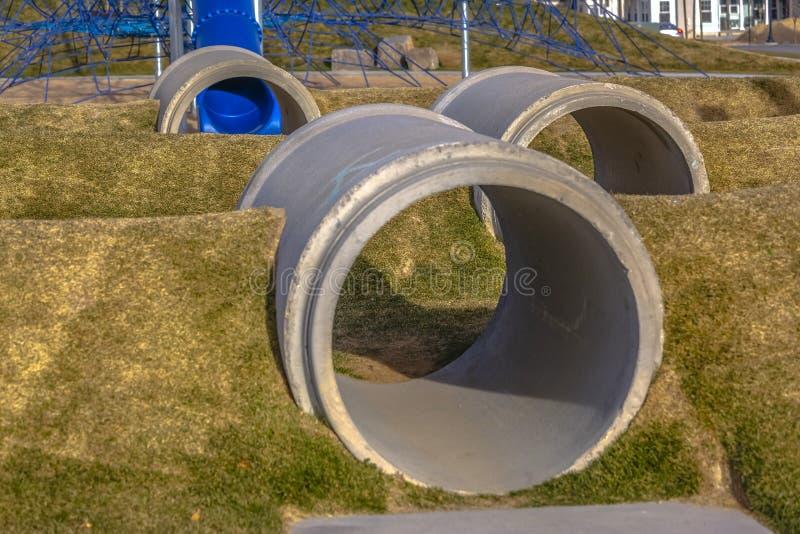 Los túneles concretos entre los montones herbosos en un patio vieron día soleado del ona imágenes de archivo libres de regalías