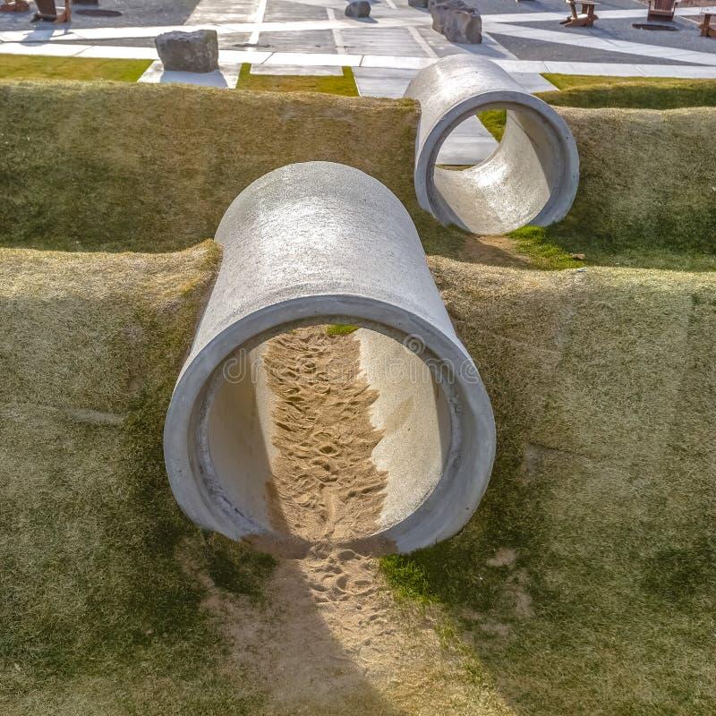 Los túneles del arrastre hicieron de los tubos concretos del cilindro en un patio soleado imagenes de archivo