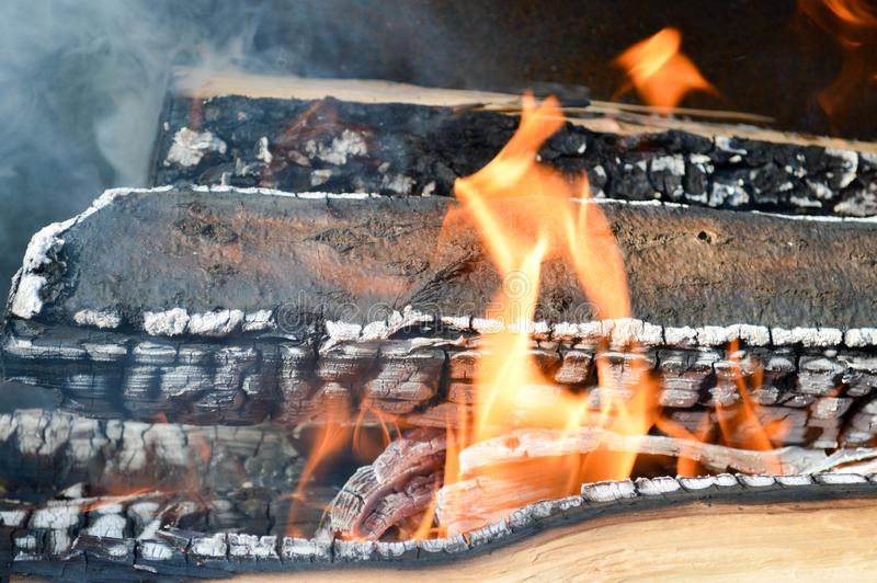 Los tablones carbonizados calientes ardientes de madera de la madera abren una sesión un fuego con las lenguas del fuego y del hu fotos de archivo