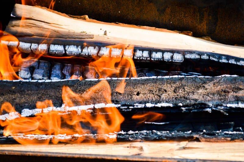 Los tablones carbonizados calientes ardientes de madera de la madera abren una sesión un fuego con las lenguas del fuego y del hu imagen de archivo libre de regalías